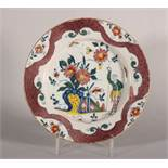 An 18th century London delft polychrome plate with reserved chinoiserie panels on a powdered