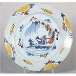 An 18th century English delft plate with polychrome landscape centre and border decoration, 8 7/8""
