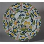 "An 18th century London delft charger with trees, flowers and fence decoration, 13 5/8"" dia ("