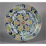 "An 18th century English delft charger with central flower decoration, 13 1/8"" dia (glaze faults"