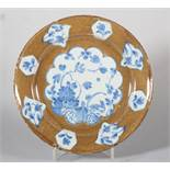 An 18th century Lambeth delft plate with powdered brown ground and reserved panels of chinoiserie