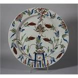 "An 18th century English delft charger with insect and vase of flowers decoration, 13"" dia ("