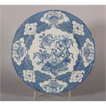 An 18th century Liverpool delft plate with chinoiserie reserved panel decoration of vase and table