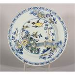 "An 18th century London delft polychrome plate with bird, root and fence decoration, 9"" dia ("