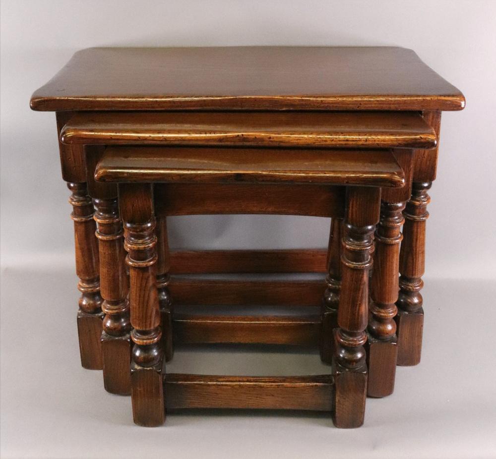 A reproduction oak nest of tables, in la