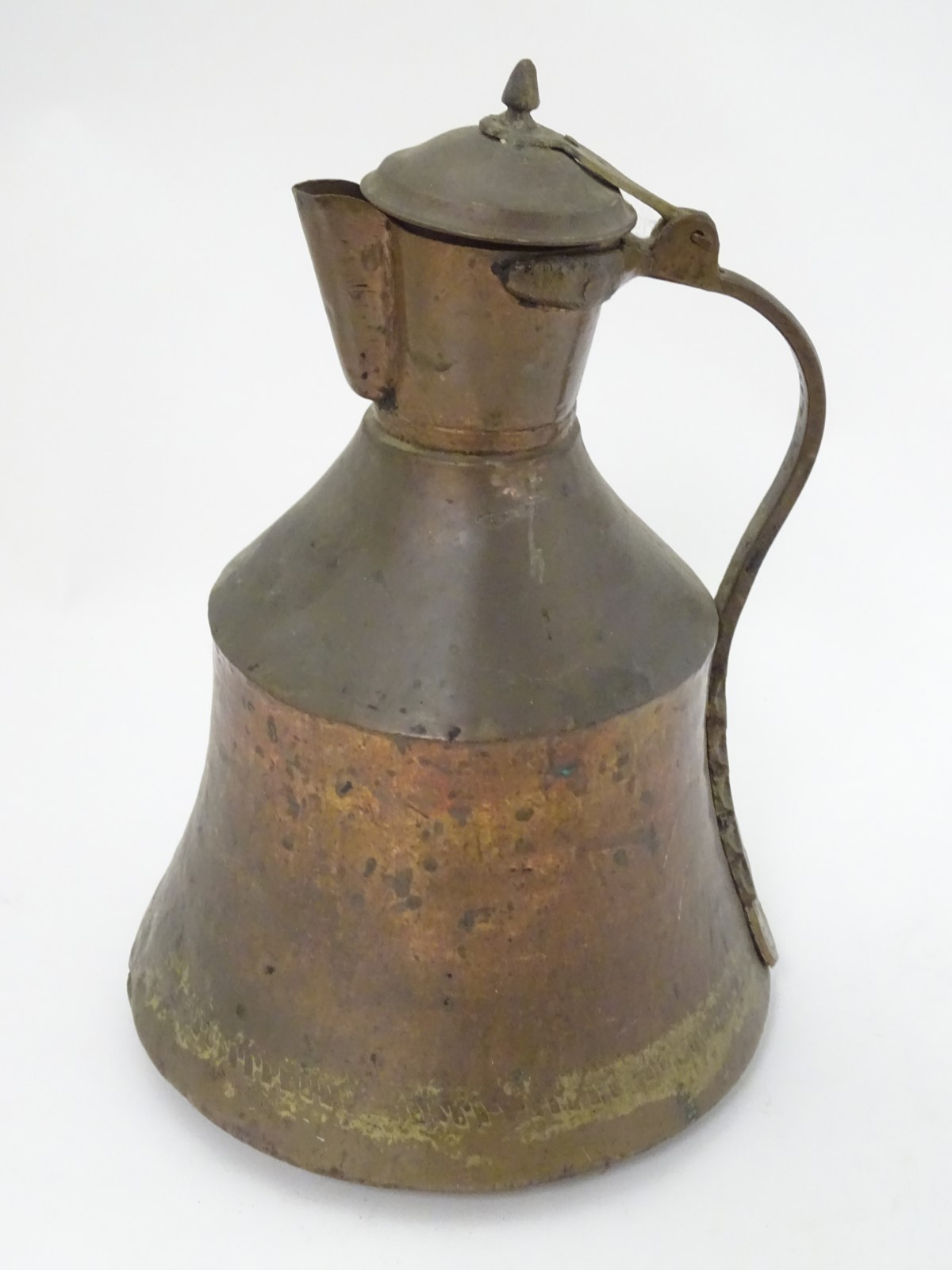 Lot 31 - An Ottoman plannished copper and brass handled lidded ewer,