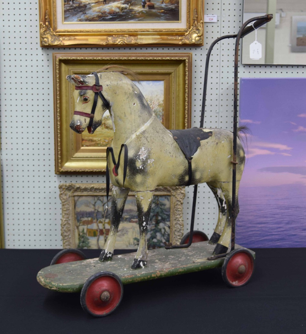 "Lot 50 - Tri-ang wooden carved painted push along horse, bearing the trademark label, 28"" high (faults)"