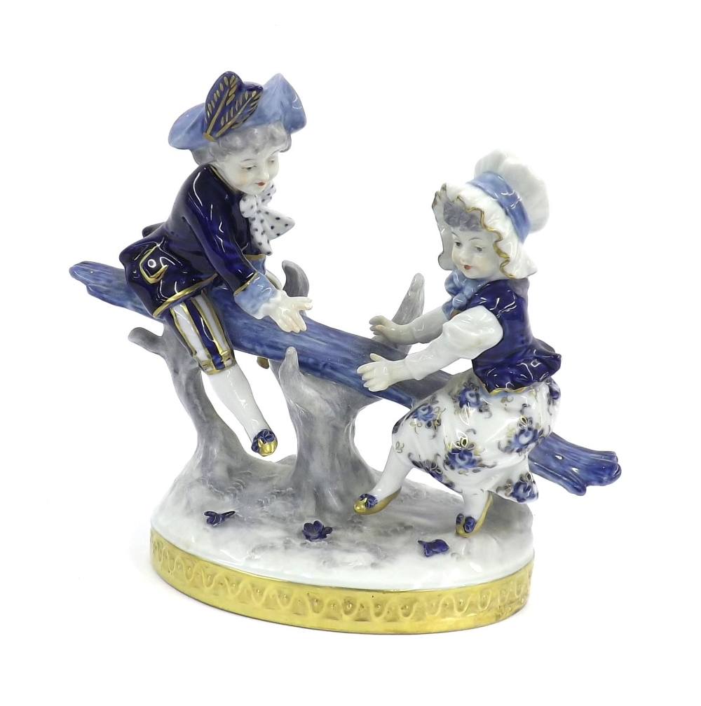 Lot 51 - German porcelain group, modelled with children on a see-saw, in blue and white glaze upon an oval