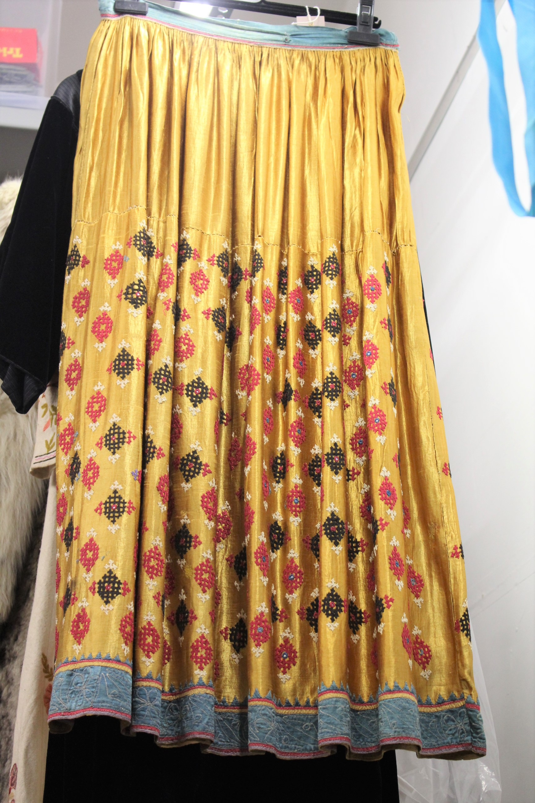 ANTIQUE INDIAN SKIRT a full length gathered skirt made from 19thc gold coloured silk, embroidered