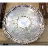 An Elkington & Co silver plated circular tray with raised leafage border and four pierced scroll