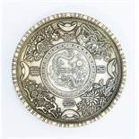 A Chinese white metal circular dish, engraved with foliage in shallow relief, inset with a Chinese