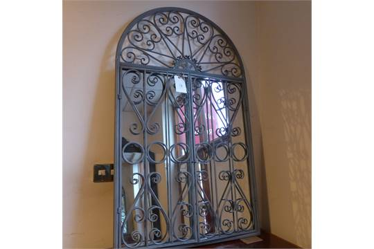 A Wrought Metal Garden Mirror With Arched Plate Within Gate Style Frame