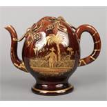 A Brameld brown glazed earthenware Cadogan hot water jug. Painted and gilded to one side with a
