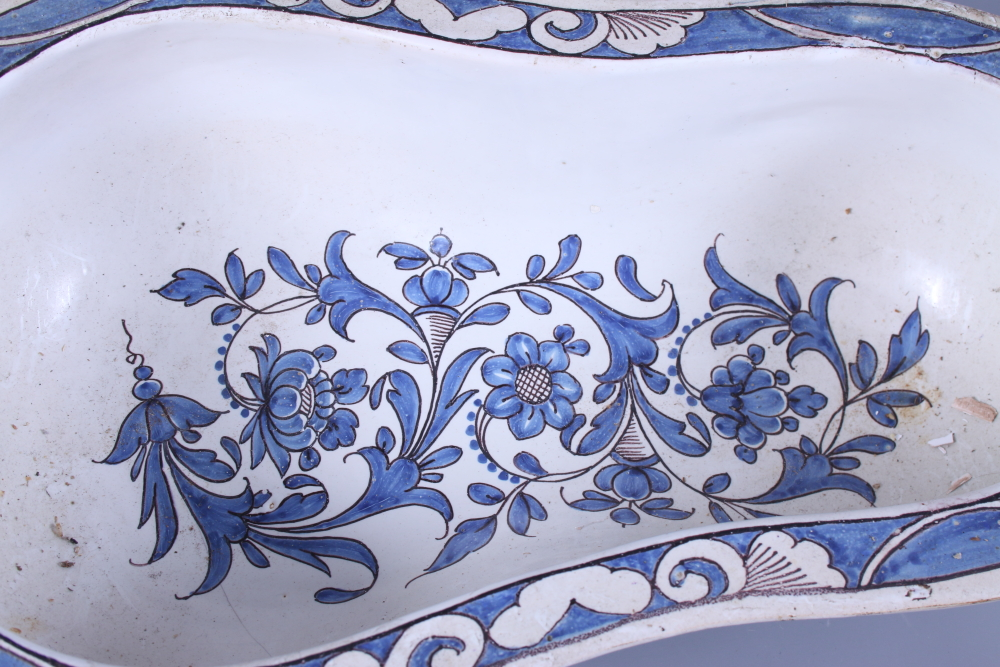 Lot 12 - A French 19th century faience painted bidet liner, decorated blue painted flowers on a white ground,