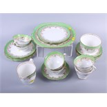 A Continental porcelain part dinner service, decorated green floral borders, sixty-five pieces