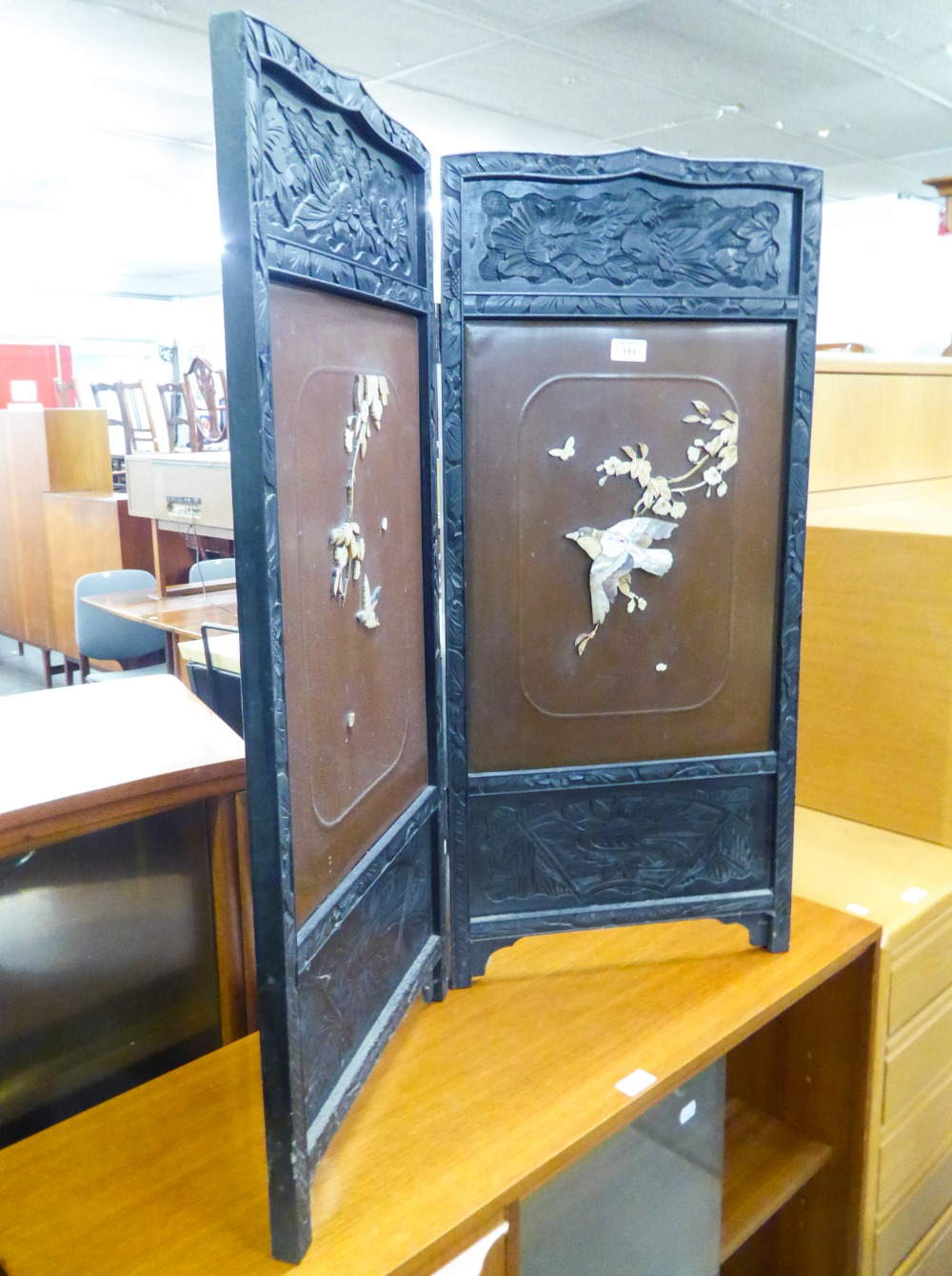 Lot 111 - AN ORIENTAL BLACK AND LACQUERED TWO-FOLD LOW SCREEN WITH BONE AND MOTHER OF PEARL APPLIED