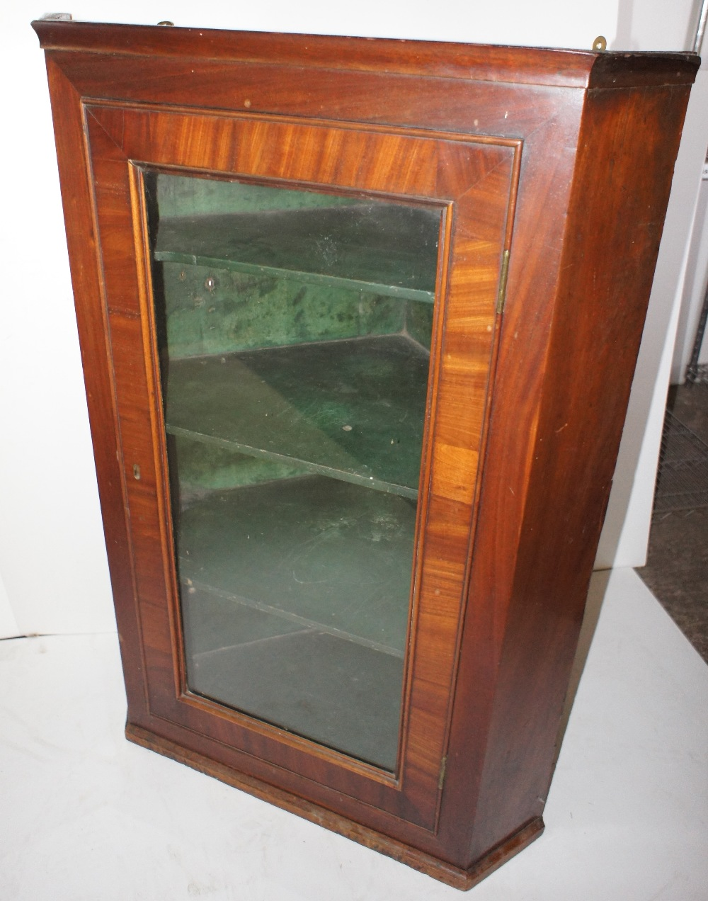 Lot 650 - NV- A mahogany wall hanging corner cabinet with a glass door enclosing a painted shelves