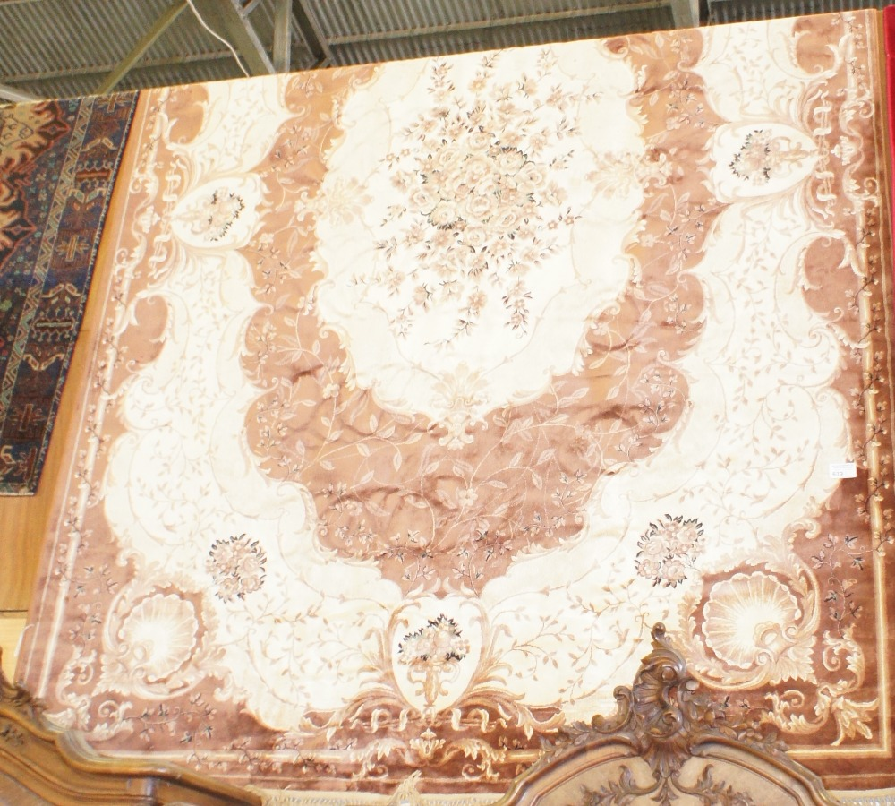 Lot 639 - NV- a large brown and white floral medallion carpet
