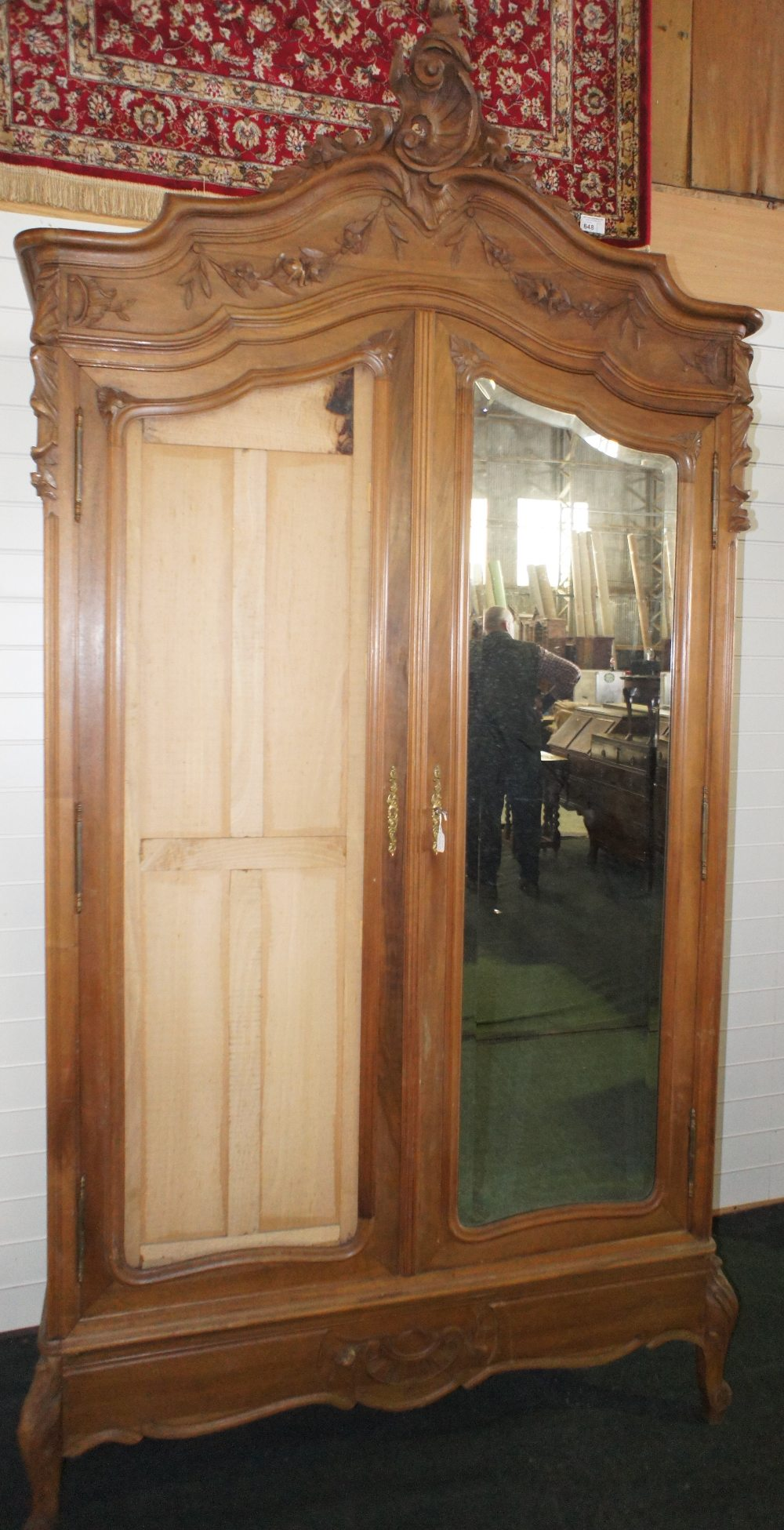Lot 611 - NV- A highly decorative carved mahogany French style armoire/wardrobe with two mirrored doors (one