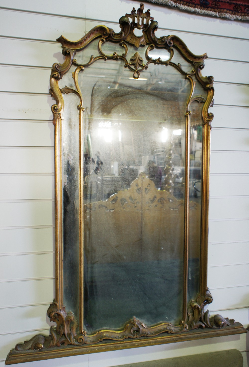 Lot 621 - NV- A large decorative wall mirror with a gilt work frame of foliate and scroll work decoration