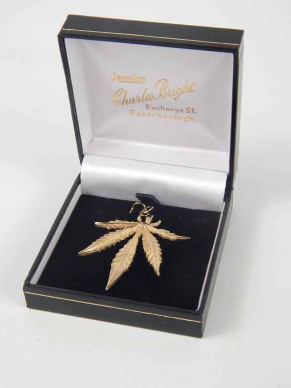 Lot 83 - A 9ct gold pendant formed as a cannabis leaf, 5.6g.