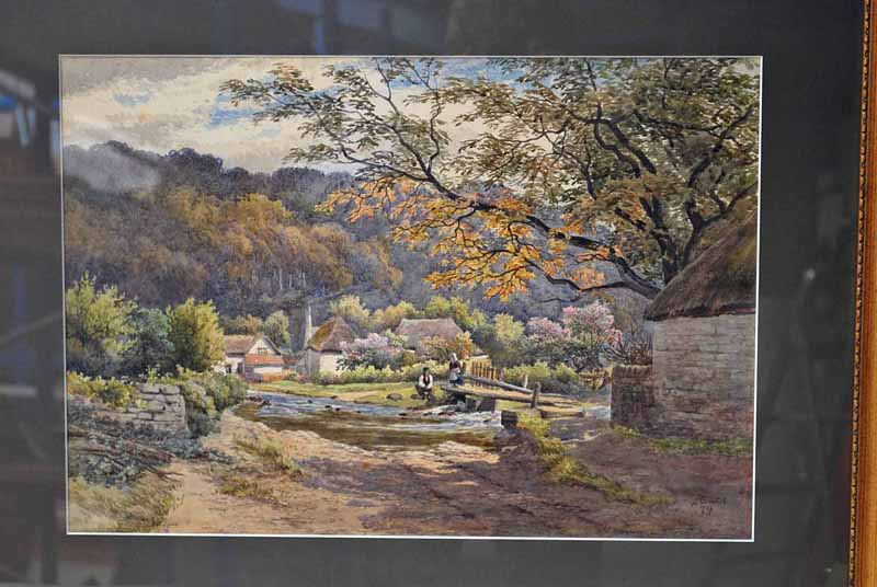 Lot 52 - William Wilde (1826-1901), Figures by a River Bridge with Hamlet and Wooded Hillside beyond,