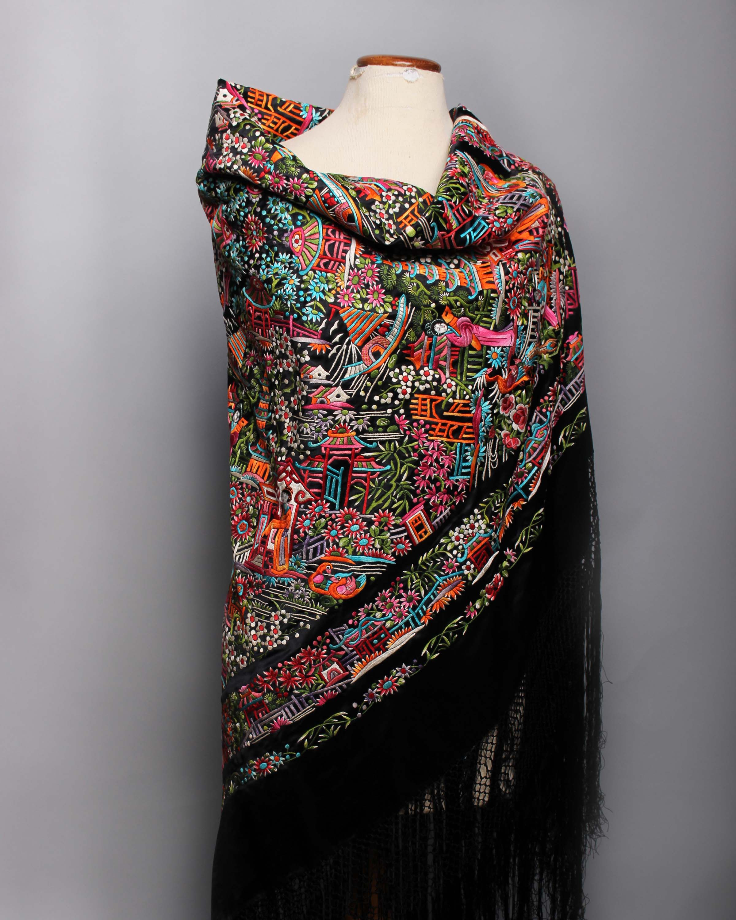 Lot 51 - An early 20th Century black silk fringed Chinese shawl, with a densely embroidered design of a