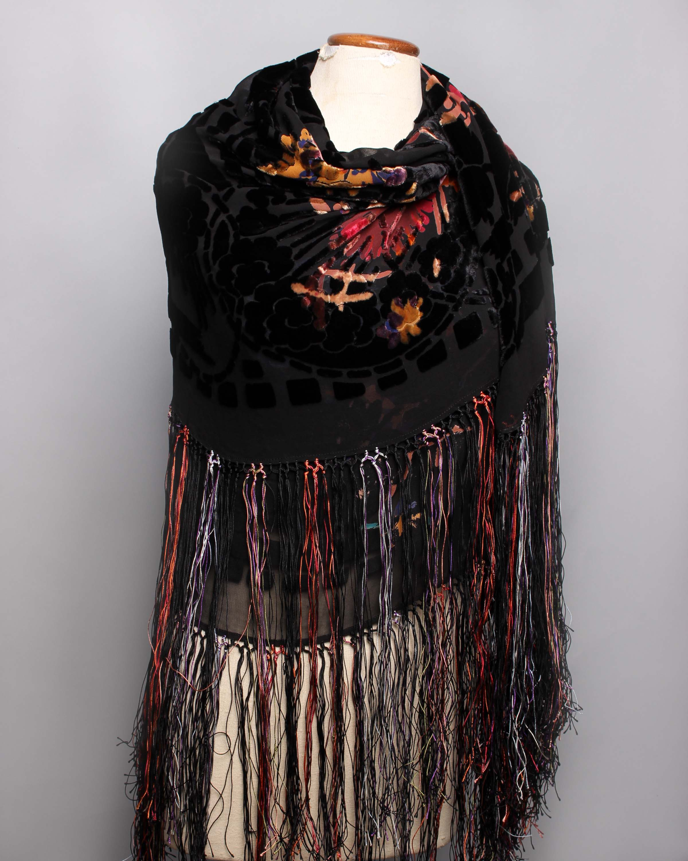 Lot 52 - An early 20th Century black silk devoré fringed shawl, decorated with colourful stylised flowers.