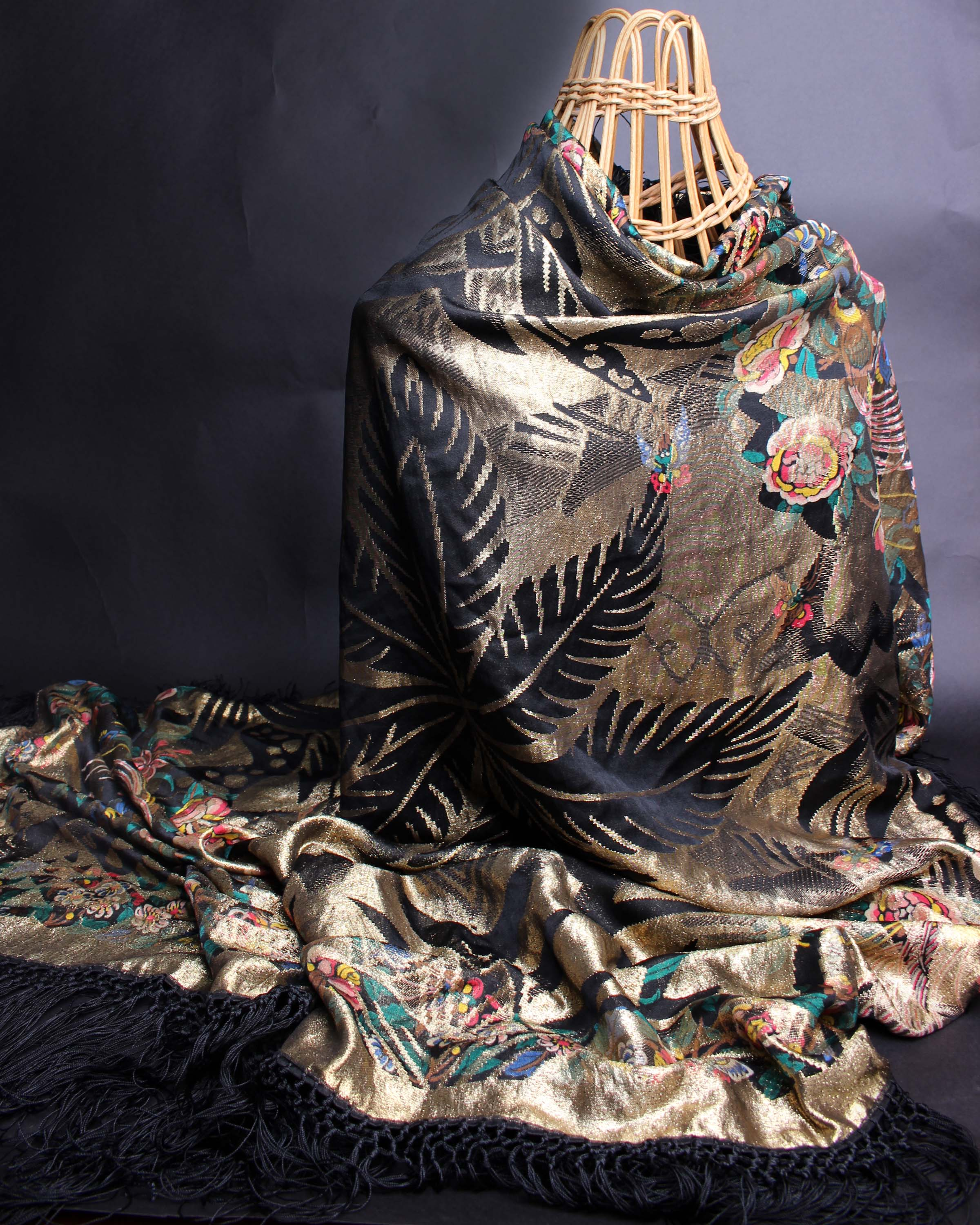 Lot 43 - An early 20th Century fringed black and gold lamé shawl, with a striking design of large palm