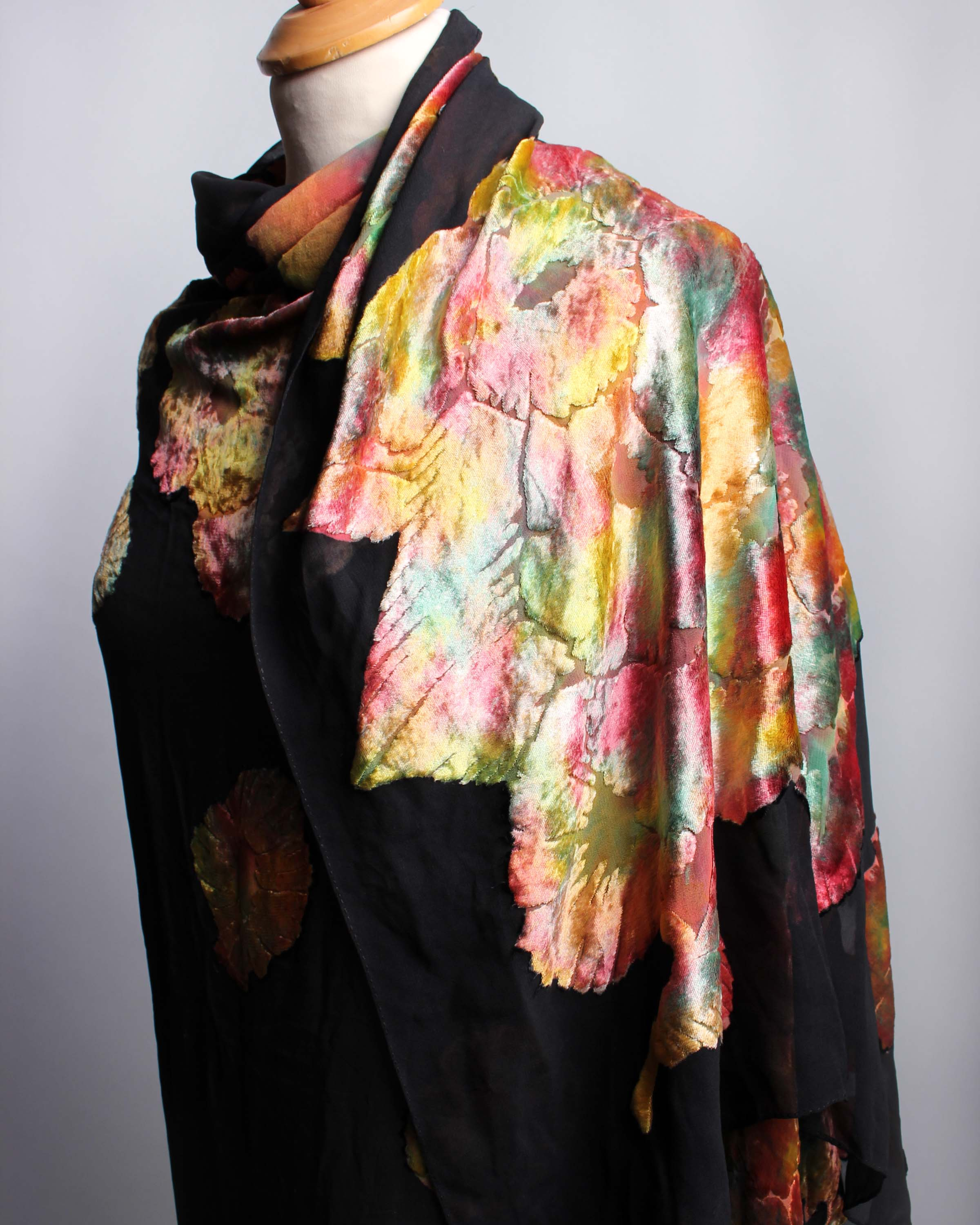 Lot 48 - An early 20th Century black silk devoré shawl, decorated with stylised brightly coloured flowers.