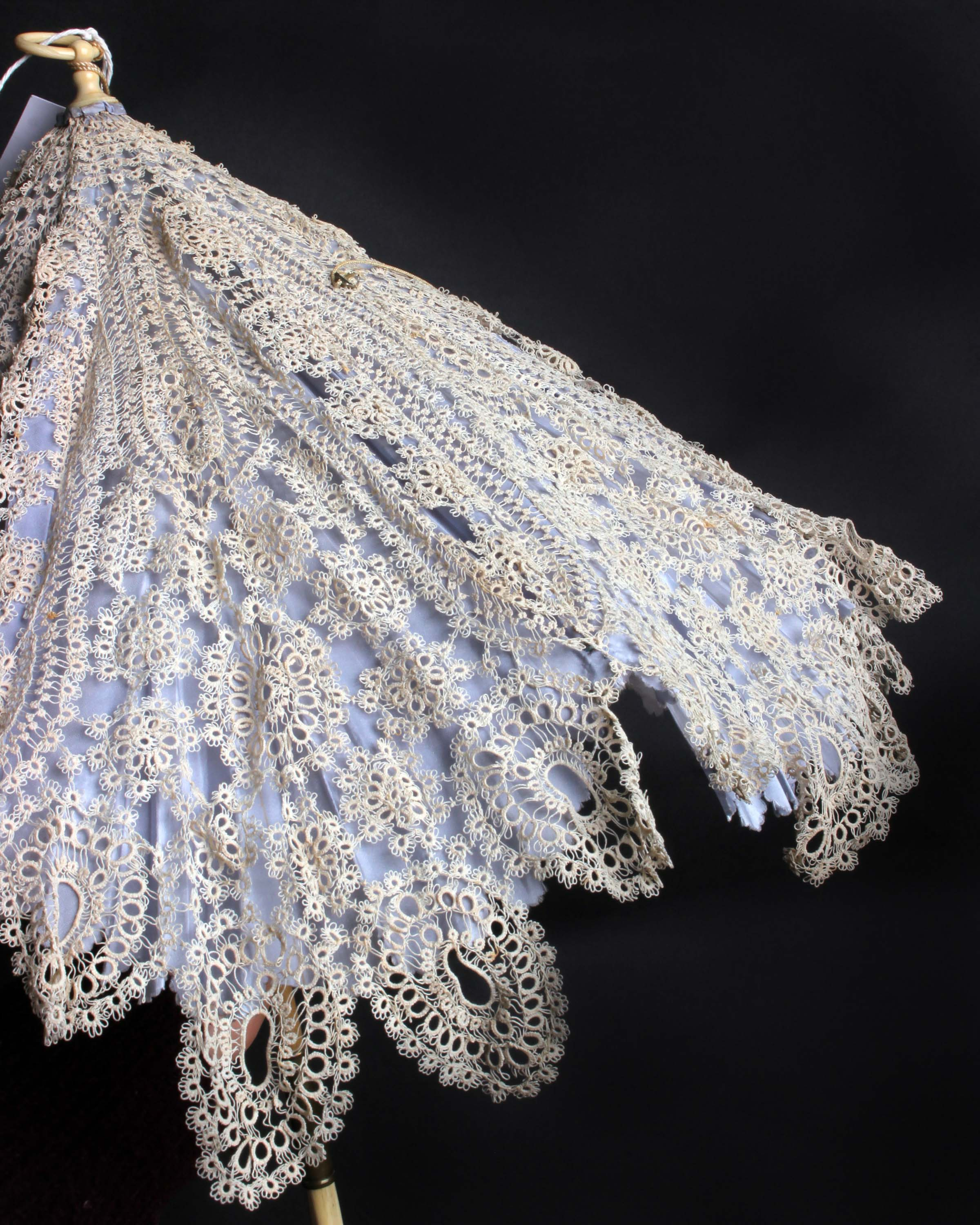 Lot 18 - A 19th Century pale blue silk lace covered hinged carriage parasol with an ivory handle, a length of