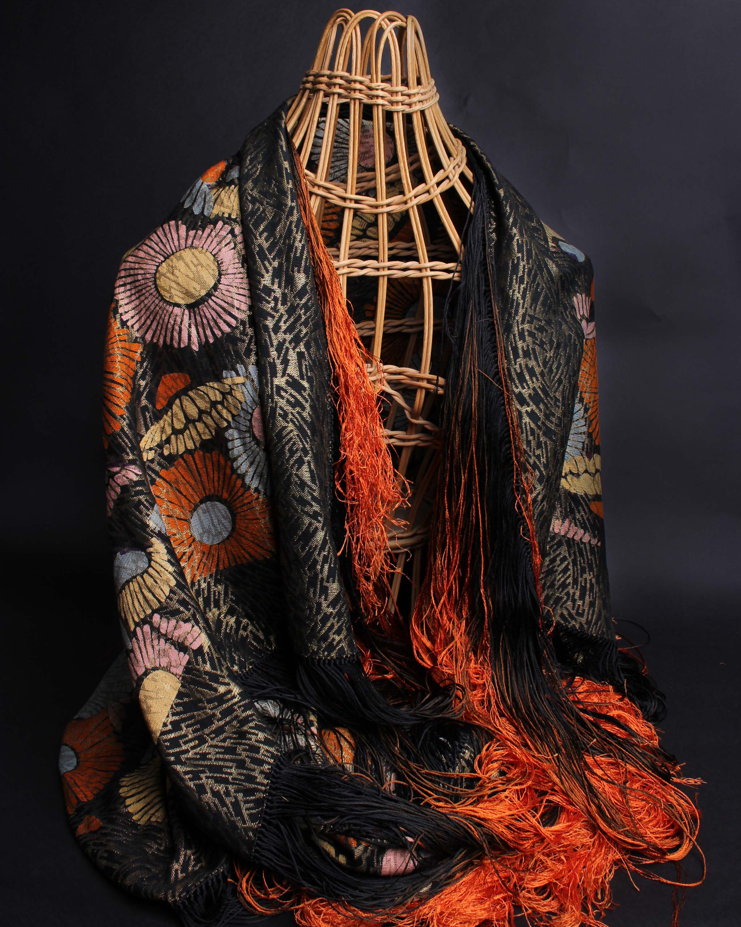 Lot 46 - An early 20th Century lamé shawl with a black and orange ombre fringe, decorated with bold pattern
