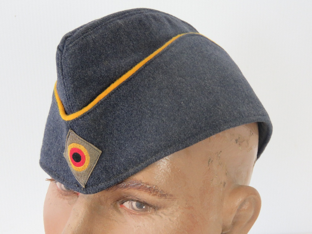 An East German blue cloth side cap havin