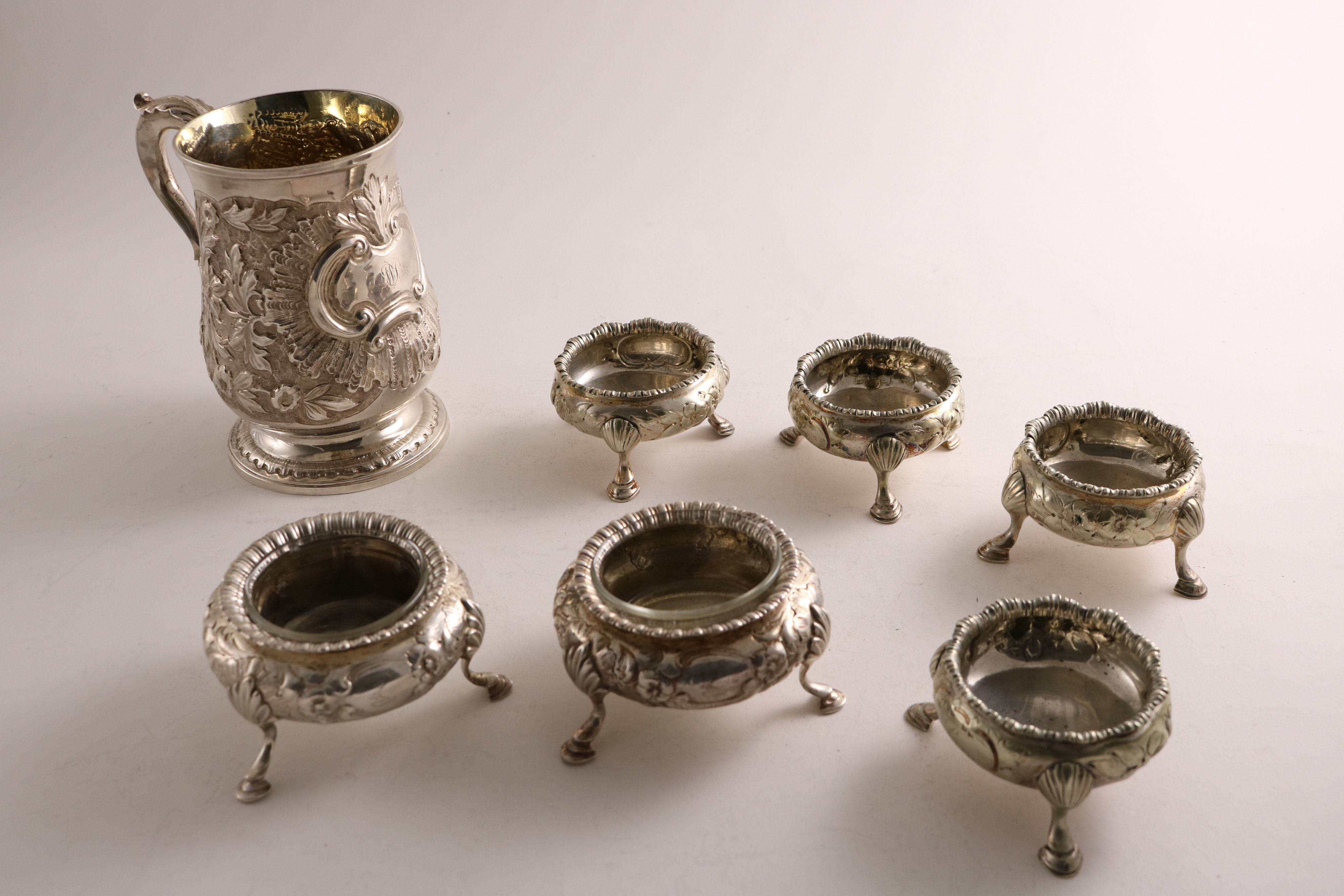 A GEORGE III SILVER MUG of baluster form with later-embossed decoration, initialled, gilt