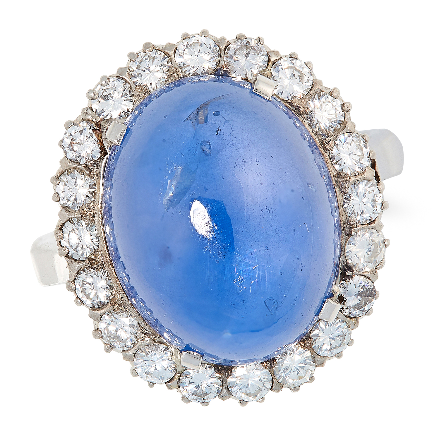 A CEYLON NO HEAT SAPPHIRE AND DIAMOND CLUSTER RING in platinum, set with a cabochon sapphire of 21.