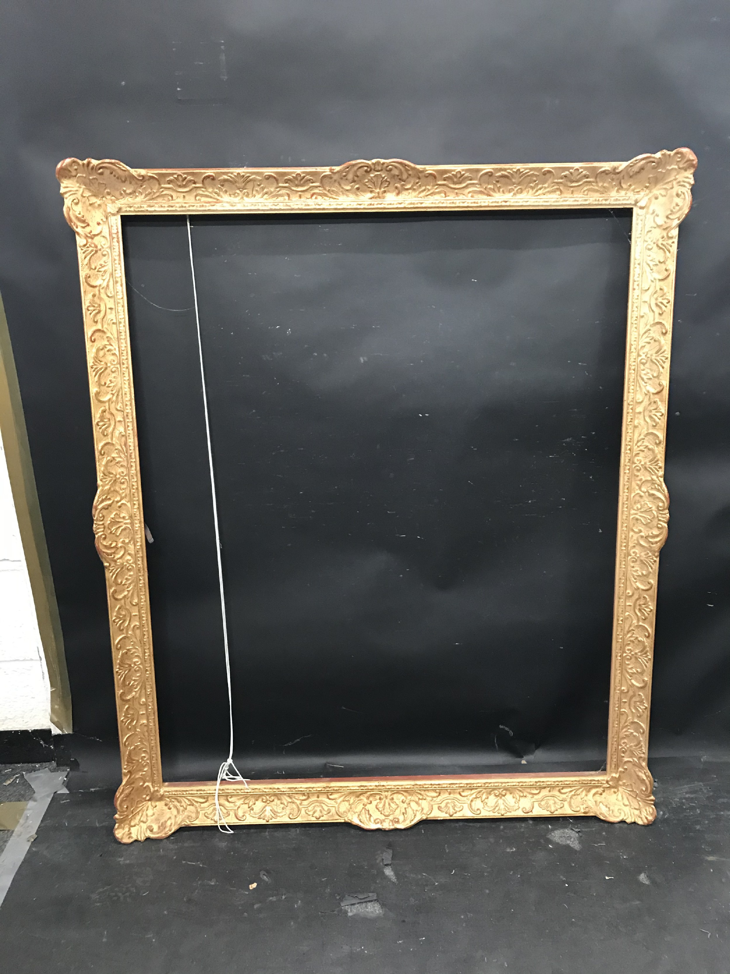 """Lot 14 - 20th Century Continental School. A Gilt Composition Frame with swept centres and corners, 43.25"""" x"""