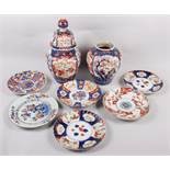 Six Imari plates of various designs, and a similar pair of vases (one with cover missing)