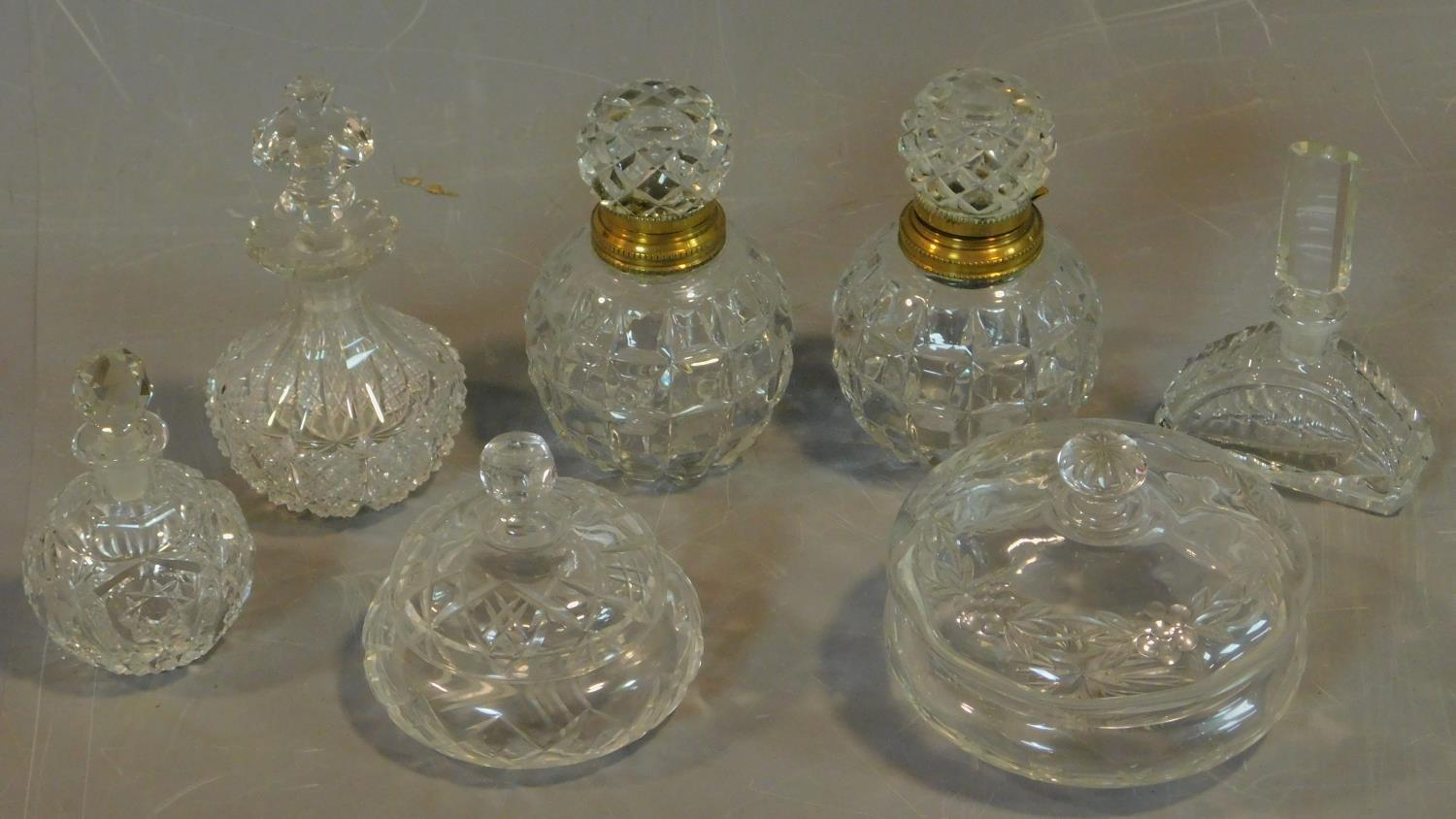 A pair of cut crystal scent bottles with gilt metal collars and a collection of other similar items.