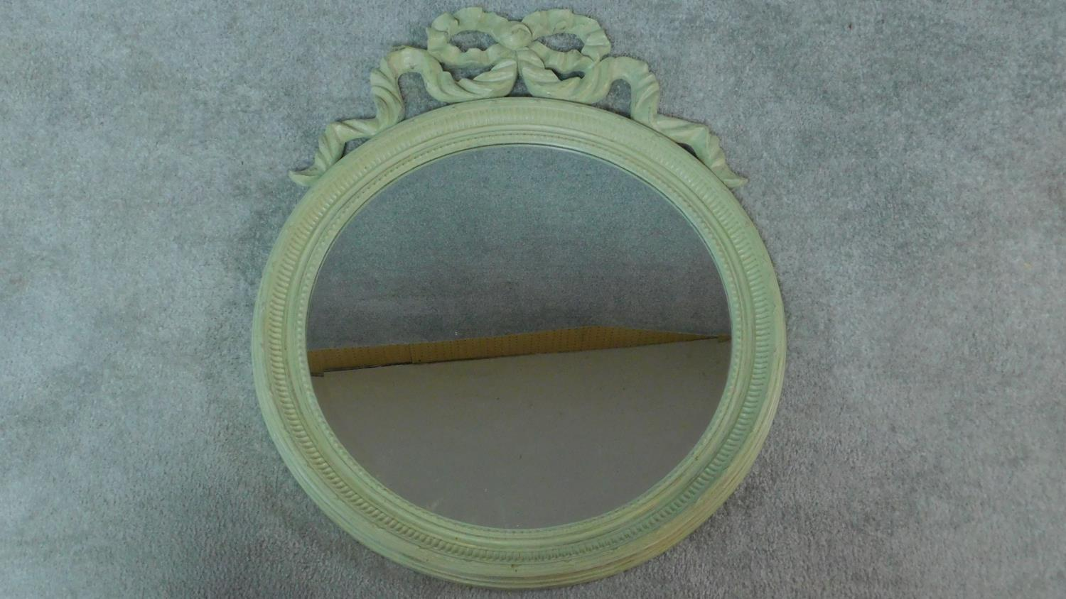 A circular painted wall mirror with ribbon cresting. 75x61cm