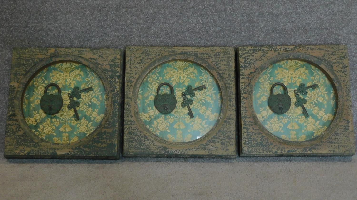 A set of three framed and glazed display cases containing old padlocks and keys. 40x40cm