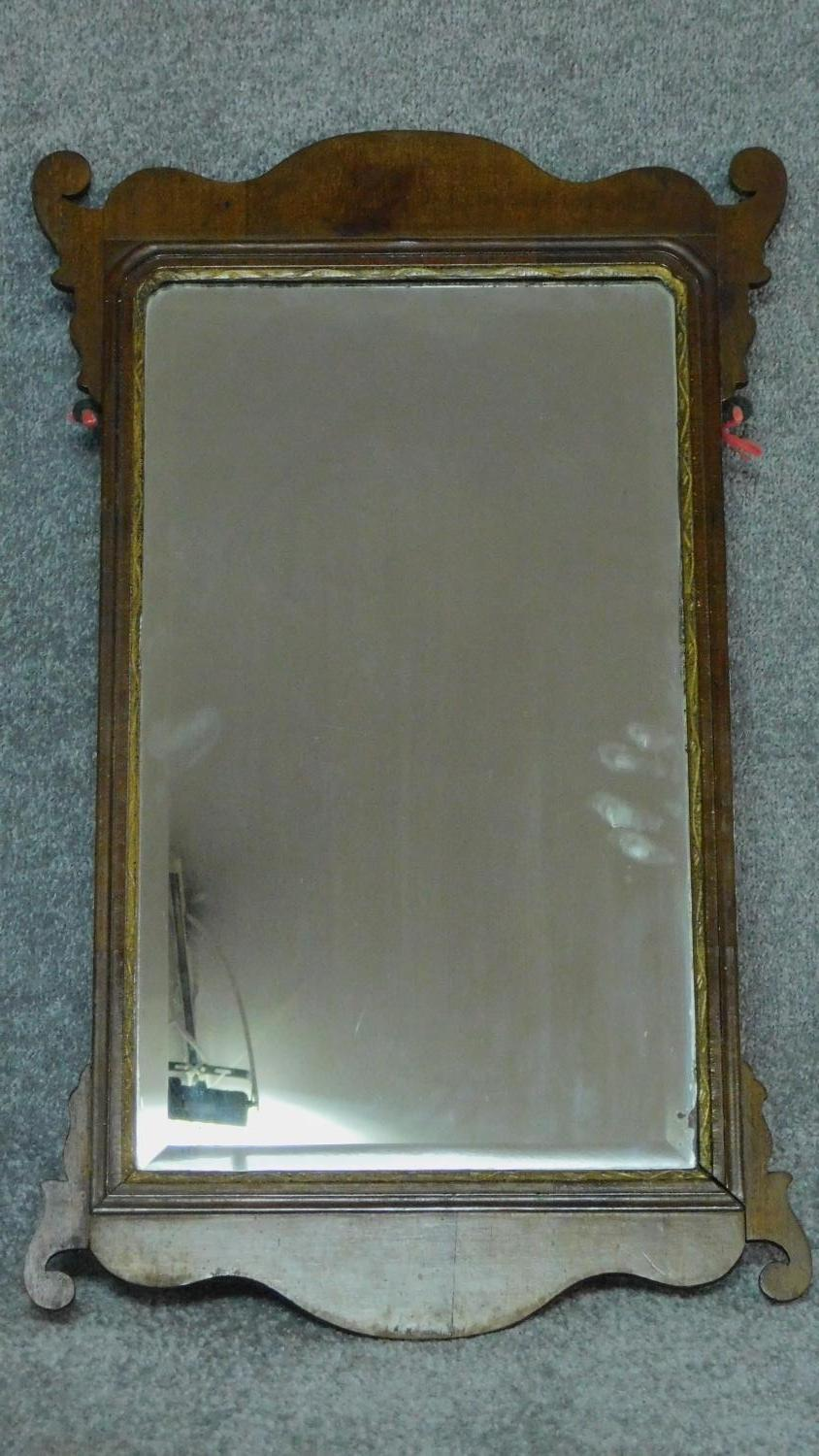 A Georgian shaped mahogany wall mirror with gilt slip and original bevelled plate. 76x47cm