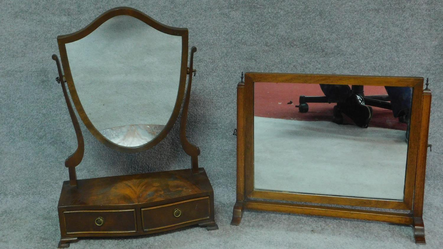 A Georgian style mahogany swing mirror with fitted base and a similar Edwardian oak mirror. H.64cm