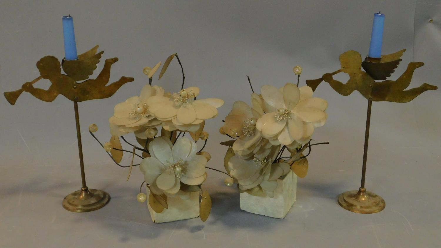 A pair of brass cherub candlesticks and a pair of mother of pearl flower arrangements. H.40cm (