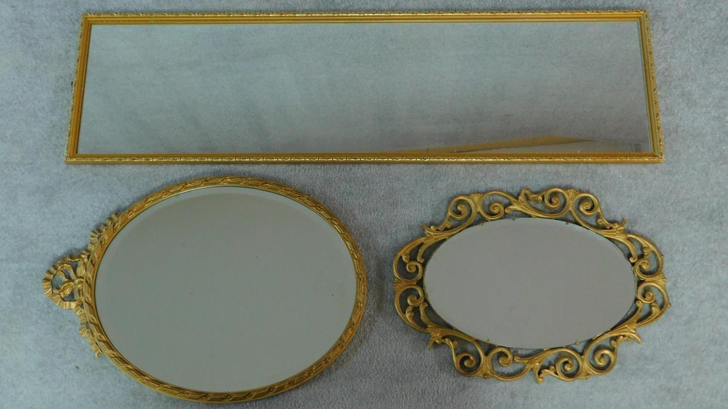 A rectangular gilt wall mirror and two oval gilt mirrors. 120x34cm