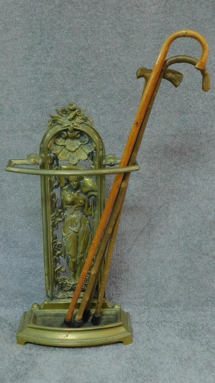 A cast metal Colebrookdale style hall stand and a collection of walking sticks. H.93
