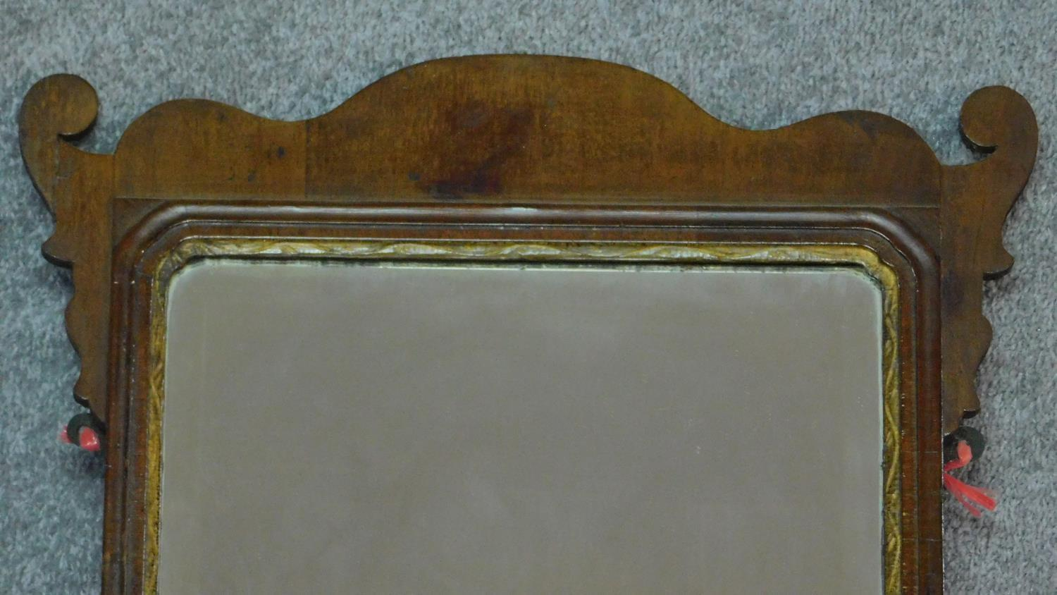 A Georgian shaped mahogany wall mirror with gilt slip and original bevelled plate. 76x47cm - Image 2 of 4