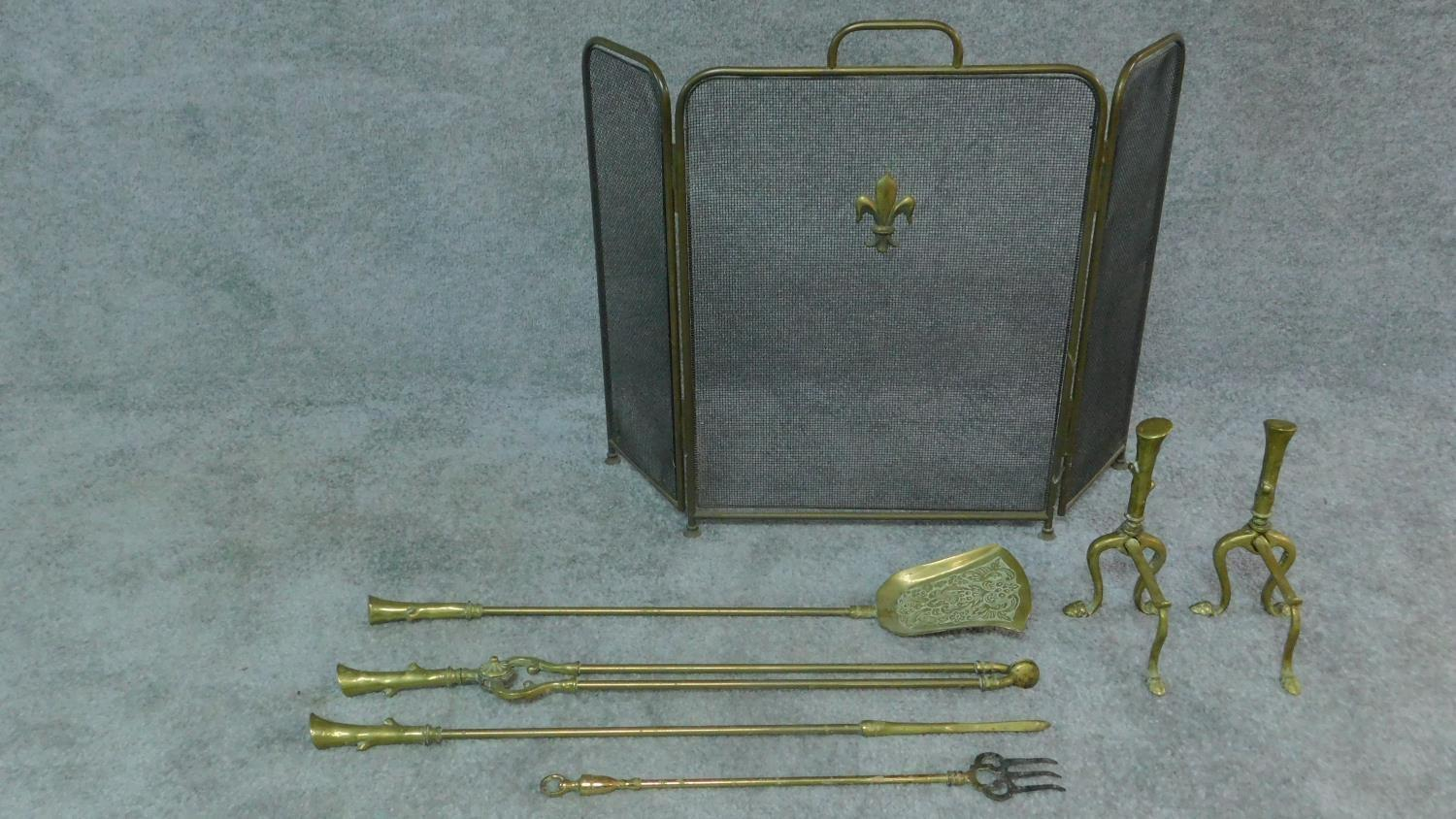 A set of 19th century brass fire implements and the matching andirons and a three section fireguard.