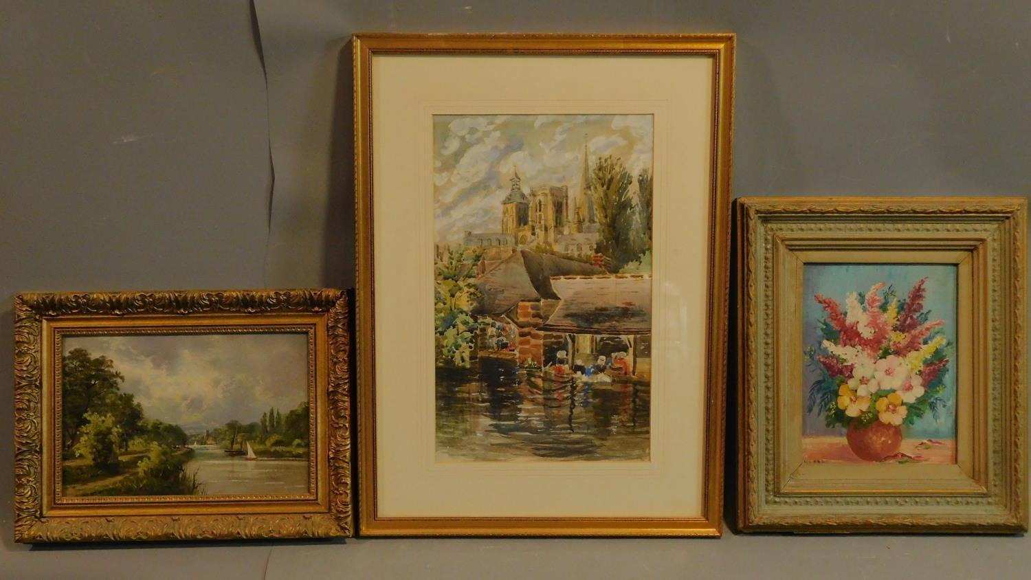 A framed and glazed watercolour, cathedral by a river, and two framed oil paintings, still life