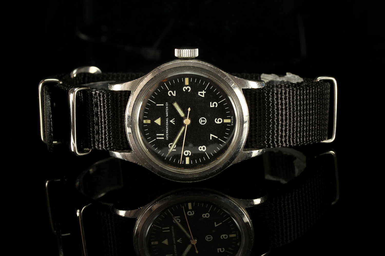 GENTLEMENS INTERNATIONAL WATCH COMPANY BRITISH MILITARY WRISTWATCH, circular black tritium dial with