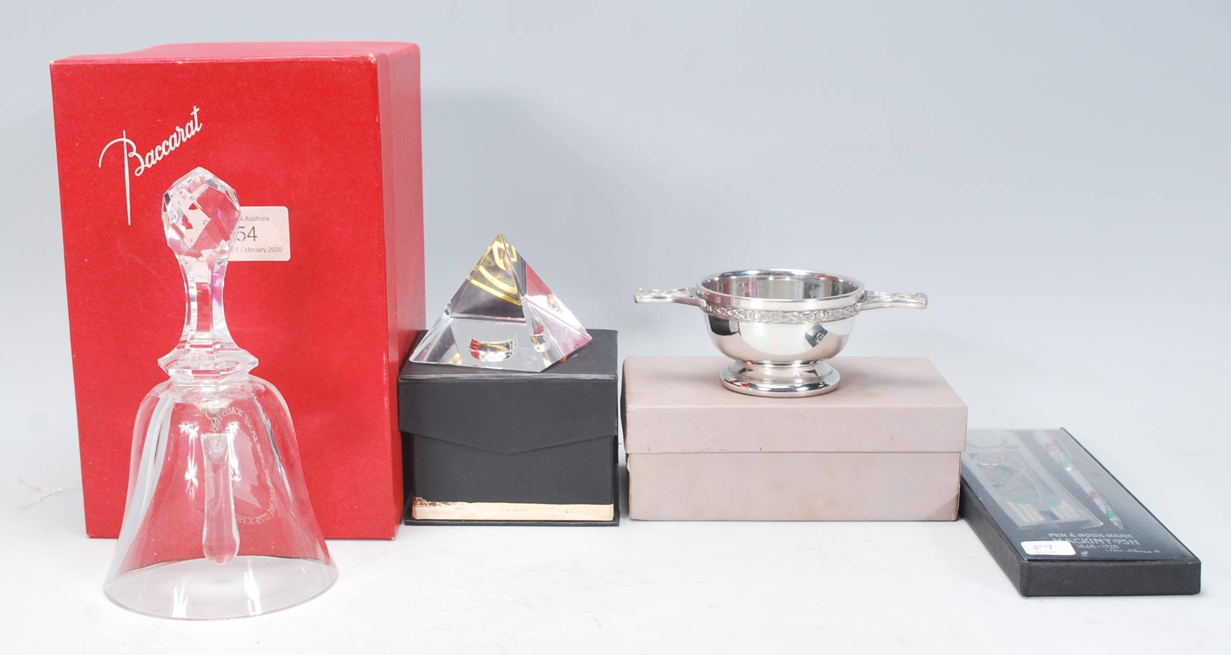 A collection of desktop items to include a Baccarat cut crystal glass commemorative bell acid etched